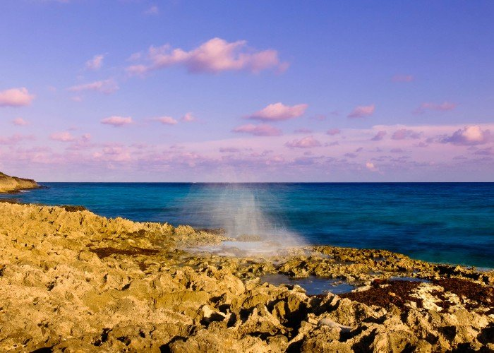 East End Cayman Islands shore with blowhole spraying water